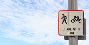 Bicycle and pedestrian shared route sign on pole post against bl Royalty Free Stock Image