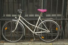 Bicycle with pink seat. Parked at iron fence Royalty Free Stock Images