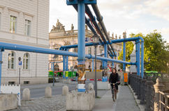 Bicycle and Pipes. BERLIN, GERMANY - SEPTEMBER 29: A young bicyclist on a sidewalk with painted blue pipes for drainage construction of a subway line on Royalty Free Stock Photo