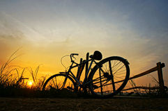 Bicycle put up at wooden fence in sunrise Royalty Free Stock Photo