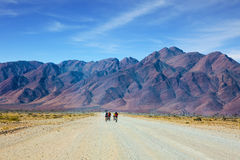 Bicycle race. Ecotourism in Africa. The dirt road in Namib-Naukluft National Park goes to distant mountains. Bicycle race in the desert of Namibia Royalty Free Stock Photo