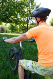 The bicycle racer against the nature. The young man on a bicycle in the sports form goes against the nature Stock Images