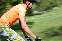 The bicycle racer in speed. The young man on a bicycle in the sports form goes at great speed Royalty Free Stock Photo