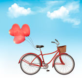 Bicycle with red heart shaped balloons in front of a blue sky Stock Images