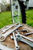 Bicycle repair. Tools, instrument for repairing bike on the wooden stump background near spokes of a wheel . Close up. Stock Photography