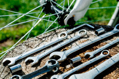 Bicycle repair. Tools, instrument for repairing bike on the wooden stump background near spokes of a wheel . Close up. Royalty Free Stock Photos