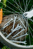 Bicycle repair. Tools, instrument for repairing bike on the wooden stump background with spokes of a wheel in the foreground. Clos Stock Photo