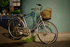 Bicycle resting against wall in Japan. Bicycle with front basket  leaning against wall in Japan Royalty Free Stock Photos