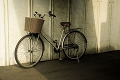 Bicycle resting against wall in Japan. Bicycle with front basket  leaning against wall in Japan Royalty Free Stock Photography