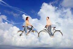 Bicycle a reunião do homem e da mulher dos pares sobre nuvens Imagem de Stock Royalty Free
