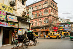 Bicycle rickshaw stops on the street corner with a traffic Royalty Free Stock Photo