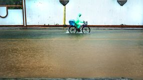 Bicycle ride on flood on the road. Flood on the road and footpath in Thamai Chanthaburi Thailand Stock Photography