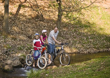 Bicycle Ride in the Park. Dad and two daughters go for an afternoon ride on their bikes Stock Photo