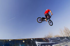 Young bmx bicycle rider. Bicycle rider in the air Royalty Free Stock Image