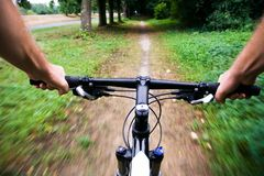 Bicycle rider in city park, blurred motion. Mountain bike rider riding real fast, motion blur Stock Photos
