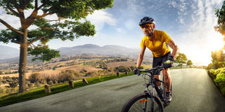 Bicycle rider cycle in Village hills nature landscape. road in motion bluring. Sunny day stock photography