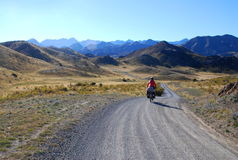Bicycle Rider in New Zealand. A woman riding her loaded touring bicycle along the remote Molesworth Road on New Zealand's South Island stock photography