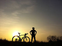 Bicycle rider stand on the hill watching the sunlight and relax Royalty Free Stock Photo