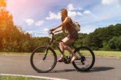 bicycle riding девушки Взгляд со стороны Лес и облака и радуга на заднем плане Стоковые Фото