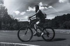 bicycle riding девушки Взгляд со стороны Лес и облака и радуга на заднем плане Черно-белое изображение Стоковое Изображение