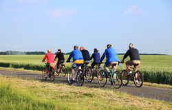 Bicycle riding. Blandainville, June 2nd 2010: A group of senior people riding their bicycles on a lane between wheat fields in Centre region of France.Riding Stock Image