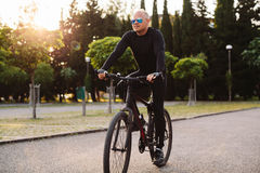 Bicycle riding male. In black sportswear and sunglasses Stock Images