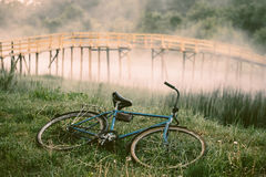 Bicycle on the river bank. Foggy morning, wooden bridge Royalty Free Stock Photos