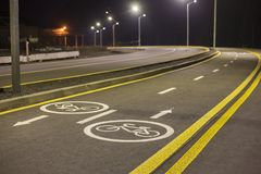 Bicycle Road Markings and Signs. Illuminated bicycle lane travel lane reserved for bicyclists with pavement markings with arrows royalty free stock photos