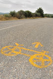 Bicycle on the road no.2. Yellow bicycle sign on the road to Santiago as marc on the pilgrimage way Stock Photo