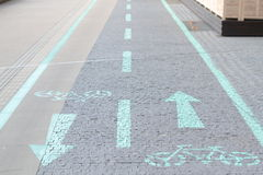 Bicycle road and pavement. Signage of pathway for bycicles with arrows showing the right side to be on Stock Photos