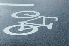Bicycle Road Sign. A Bicycle Road Sign on the Side on Wet Tarmac Royalty Free Stock Photos