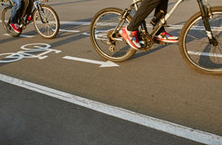 Bicycle road sign and two bike riders Royalty Free Stock Image