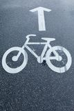 Bicycle road sign and White Arrow. Bicycle Road Sign on Wet Tarmac and a White Arrow Royalty Free Stock Images