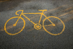 Bicycle road of sign. Yellow bicycle road sign painted on the asphalt road Stock Photography