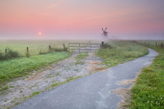 Bicycle road to windmill in fog Stock Images