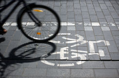 Bicycle route. Sign on the street and motion blurred bicycle wheel Royalty Free Stock Images