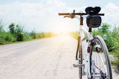bicycle on rural road with grass at sunset royalty free stock photography