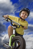 Bicycle Safety for Youth. Young boy riding his bicycle with his safety helmet on Royalty Free Stock Image