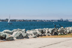 Bicycle, Sailboat, Military Vessels, and City of Coronado in Background Royalty Free Stock Image