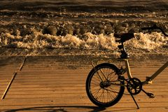 Bicycle on the seashore in sepia style. Waves in the background royalty free stock image