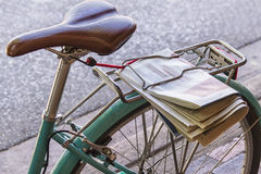 Bicycle seat and wheel. Closeup of bicycle seat and wheel with newspaper on sidewalk Royalty Free Stock Photo