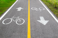 Bicycle sign and arrow sign on the road Stock Photos