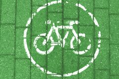 White bicycle icon on green brick background, toned royalty free stock image