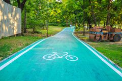 A bicycle sign on bike lane in the park with nature background. A bicycle sign on green bike lane in the park with an old road roller and nature background Royalty Free Stock Photography