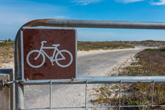 Bicycle Sign on Metal Gate. In front of sandy dirt road Royalty Free Stock Images