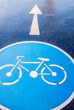 Bicycle sign on pavement road. Blue bicycle sign on pavement road  after rain Royalty Free Stock Images