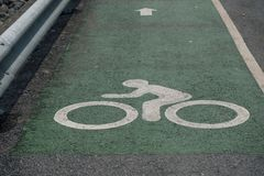 Bicycle sign on the road with green ground for cycling safety stock image