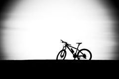 Bicycle silhouette in black and white. On the road Royalty Free Stock Photos