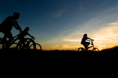 Bicycle silhouette. Family cycling exercise during sunset stock photography