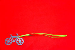 Bicycle silhouette on a red background. Bicycle silhouette with green ribbon on a red background stock image